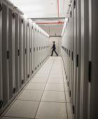 Technician walking in server hallway in large data center