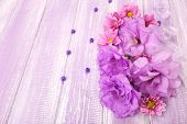beautiful chrysanthemum and artificial eustoma flowers on purple wooden background