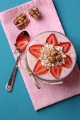 Healthy breakfast - yogurt with  strawberries and muesli served in glass jar, on color wooden backgr