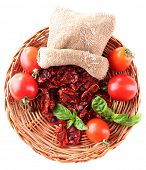 Sun dried tomatoes, fresh tomatoes on wicker mat,  basil leaves, isolated on white