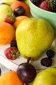 Ripe fruits and berries in bowl on table close up