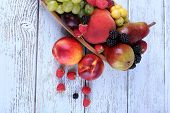 Different berries and fruits on wooden table close-up