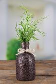Vase with estragon on a wooden table on bright background