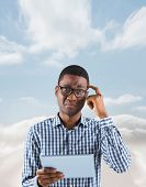 Young businessman thinking and holding tablet against cloudy sky