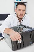Computer engineer listening to console with stethoscope in his office
