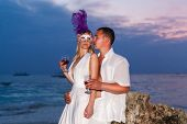 Bride And Groom On A Tropical Beach Drinking Wine From Glasses With The Sunset In The Background