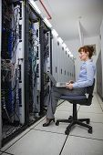 Technician sitting on swivel chair using laptop to diagnose servers in large data center