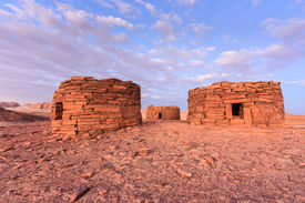 image of empty tomb  - Ancient Nabatean tombs glown purple in a desert sunset - JPG