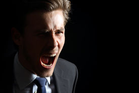 image of shout  - Angry businessman shouting isolated in a black background - JPG