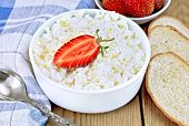Curd with strawberries in bowl and bread on board