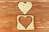 Slice of cereal toast bread with cut out heart shape on wooden background