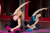 Two Pretty Girls Do Body Bending On Mats In Fitness Center