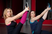 Two Smiling Girls Do Stretching Exercises In Fitness Center