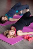 Two Girls Do Aerobics Exercises On Mats In Fitness Center