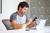 Casually Dressed Man Using Mobile Phone In Design Studio
