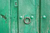 Old run-down green painted wooden door and iron nails