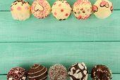 Tasty cake pops on wooden table