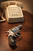 MARYLAND, USA - CIRCA DEC 2014: A staged close-up of an H & R .32 caliber pistol next to a telephone on a brown wooden nightstand table, shallow depth of field.