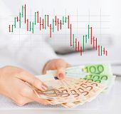 business, people and finances concept - close up of woman hands holding euro money over gray background with forex chart
