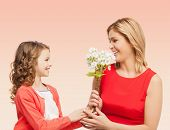 people, holidays, relations and family concept - happy little daughter giving flowers to her mother over beige background
