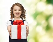 people, childhood, summer and holidays concept - happy smiling girl with gift box over green background