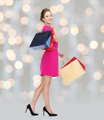 people, holidays and sale concept - young happy woman with shopping bags over holidays lights background