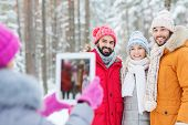 technology, season, friendship and people concept - group of smiling men and women taking picture with tablet pc computer in winter forest