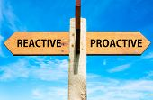 stock photo of persistence  - Wooden signpost with two opposite arrows over clear blue sky Reactive versus Proactive messages Behaviour conceptual image - JPG
