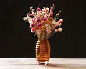 Bouquet of dried flowers in vase on table and dark background