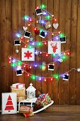 Garland in shape of Christmas tree on wooden wall background, gift boxes and lantern. Christmas atmosphere concept