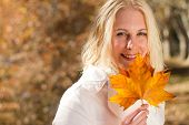 woman holding autumn leaf