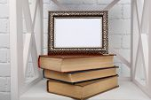 Photo frame with books on shelf, on