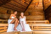 stock photo of sauna  - Senior and young woman in sauna sweating in heat - JPG