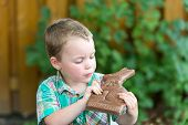 Little Boy Looking At A Chocolate Bunny In His Hands