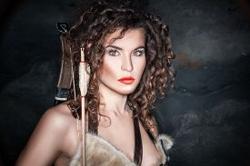 stock photo of bow arrow  - Amazon girl with bow and arrow dressed in animal skins - JPG