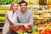 stock photo of grocery cart  - Cheerful young couple smiling at camera and standing behind their shopping cart in a food store  - JPG