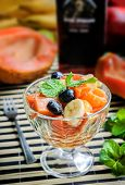 picture of papaya  - Healthy salad with a papaya dark grapes tangerines banana decorated with mint leaves selective focus - JPG