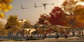 image of pterodactyl  - Three flying Eudimorphodons pass a group of Coelophysis hunting for prey through a forest of autumn trees in the Triassic Period - JPG