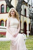 picture of evening gown  - Beautiful blond curly woman wearing evening peach color gown sitting on white bench outdoors - JPG