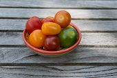 picture of ceramic bowl  - Group of tiny tomatoes in a ceramic bowl sitting on a wooden surface - JPG