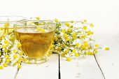 pic of chamomile  - cup of chamomile tea with chamomile flowers on white wooden planks - JPG
