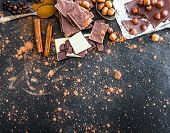 foto of chocolate spoon  - Chocolate in plates and spices in the spoons on black table - JPG