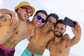 stock photo of bachelor party  - Group of four male friend taking a selfie at the beach - JPG
