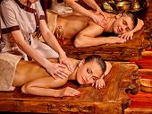 stock photo of ayurveda  - Loving couple  having oil Ayurveda spa treatment on wooden bed - JPG