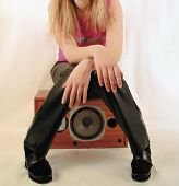 stock photo of groupies  - young girl with long blonde hair and leather trousers sitting on speaker