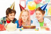 foto of teen smoking  - Beautiful teen girl blow cake candles on birthday cake with friends with party caps and balloons presents and decorations around - JPG