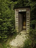 stock photo of hillbilly  - an outhouse pretending to be a telephone booth - JPG
