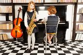 image of saxophones  - Two girls in school uniform dresses playing on the alto saxophone and the piano indoors with black and white checked floor - JPG