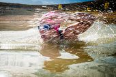 pic of dam  - An active female is seen swimming across a dam while wearing a pink swimming cap - JPG