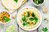 stock photo of chickpea  - vegan tortilla with roasted broccoli and chickpeas and avocado sauce - JPG